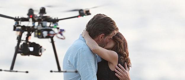 L'attore Pierce Brosnan bacia l'attrice Salma Hayek sul set, mentre un drone li riprende